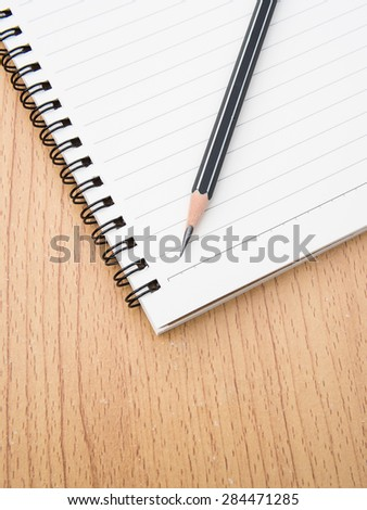 Pencil on ring binding notebook with wooden background, Selective focus on pencil sharpness - stock photo