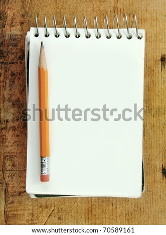 Pencil on small notepad blank for your text. - stock photo