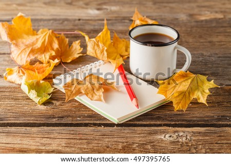 pencil on the empty vintage paper, autumn leaves on wooden table. Back to school concept: paper, pencils and colorful leaves.