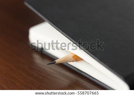 Pencil on the pages of an closed notebook
