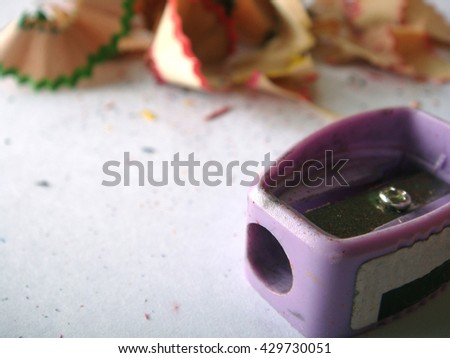 pencil sharpener and Fragments of colored pencils - stock photo