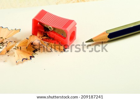 pencil sharpener, pencil and shavings on white background - stock photo