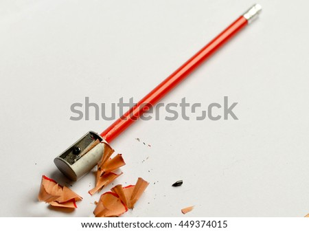 Pencil sharpener, pencil shavings and red graphite pencil, isolated on white background - stock photo