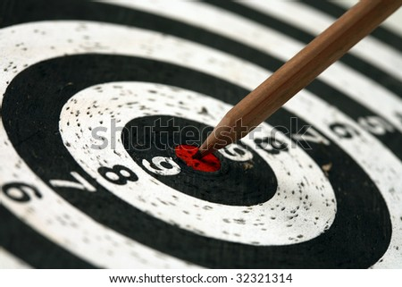 Pencil sticks out in the target for darts - stock photo