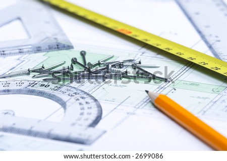 Pencil, tape measure, nails and geometric tools on top of a floor plan. Focus on nails.