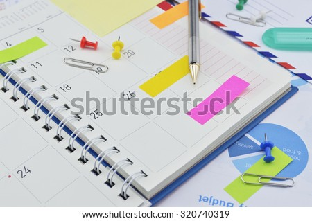 Pencil with colorful sticky notes and pin on business diary page - stock photo