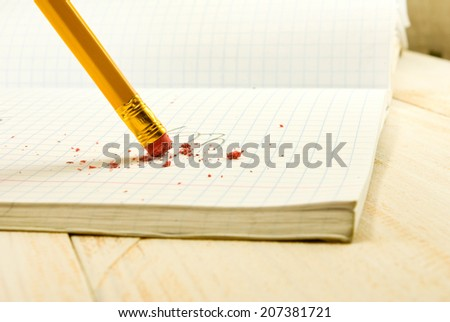 pencil with eraser on exercise book background closeup - stock photo