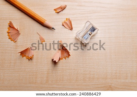 Pencil with sharpening shavings on wooden background - stock photo