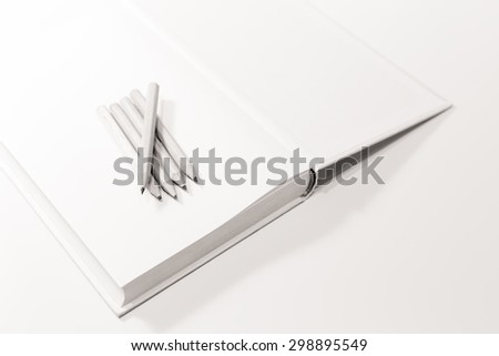 Penciles on a blank note book in black and white with selective focus and shallow depth of field.