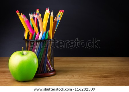 Pencils and apple on table - stock photo