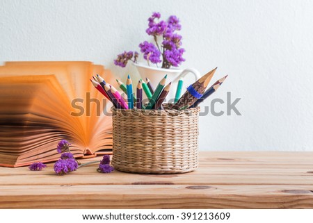 Pencils and colored pencils in the basket and open book with purple flowers in a white vase on a wooden table, selective focus