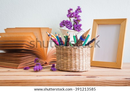 Pencils and colored pencils in the basket, open book, purple flowers in a white vase and wooden photo frame on a wooden table, selective focus - stock photo