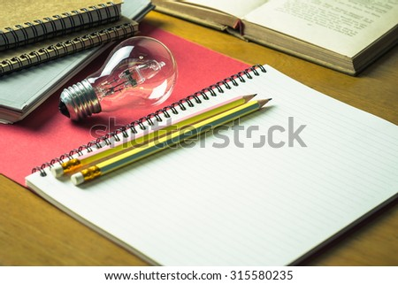 Pencils and light bulb on notebook for creative writing concept