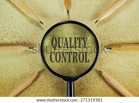 Pencils and magnifier in a conceptual image about controlling the quality - stock photo