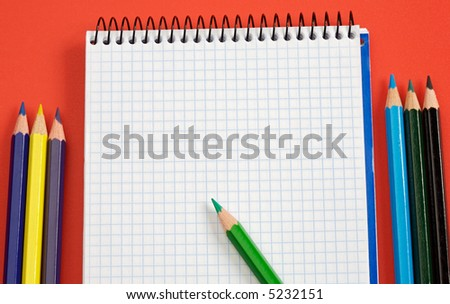 pencils and notebook over a red background - stock photo