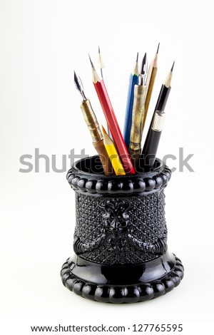 pencils and pens in the glass holder - stock photo