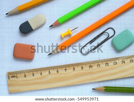 Pencils and wooden ruler on a graph paper