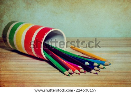 pencils colour on wooden table over grunge background