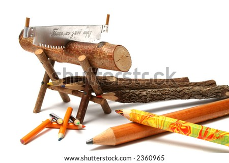 Pencils from natural wood of various type and the size near to a saw and a log - stock photo