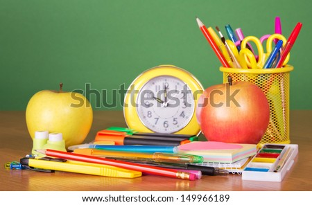 Pencils, handles, scissors in a support, an alarm clock and two apples, on a green background