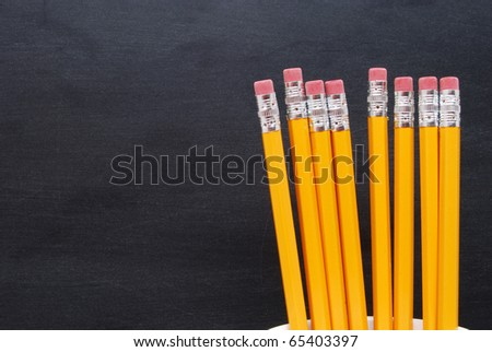 pencils in cup in front of blackboard