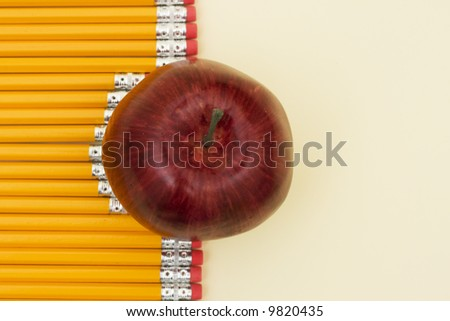 Pencils lined in a row with apple with copy space