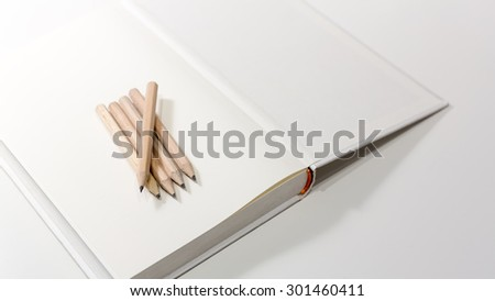 Pencils on a blank note book in black and white with selective focus and shallow depth of field. - stock photo
