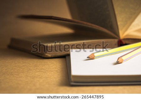 Pencils on notebook with old opened book