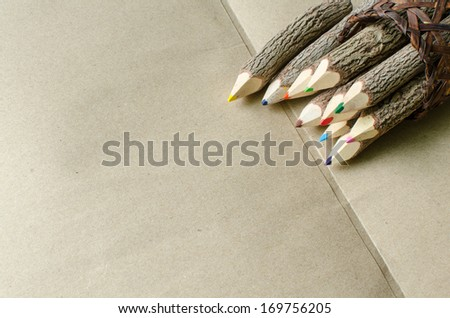 pencils stylized tree branch on brown paper background - stock photo