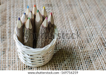 pencils stylized tree branch on rattan weaves background - stock photo