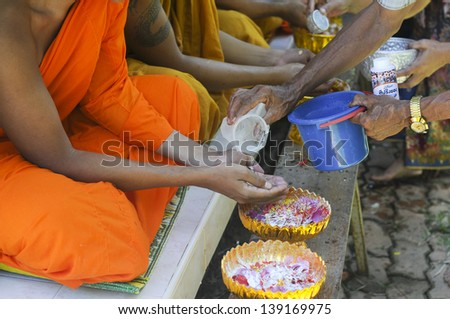 "PENDANG,MALAYSIA - APRIL 13: Unidentified Thai people showering monk in ""Songkran Festival 2012(water festival)"" at temple on April 13,2012 in Pendang, Kedah, Malaysia - stock photo"