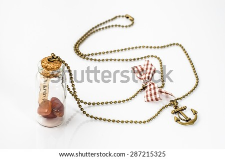 Pendant made with glass bottle, antique gold chain and amber isolated on white background. Handmade jewelry.