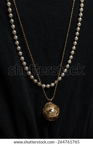 Pendant with pearls on a black background - stock photo