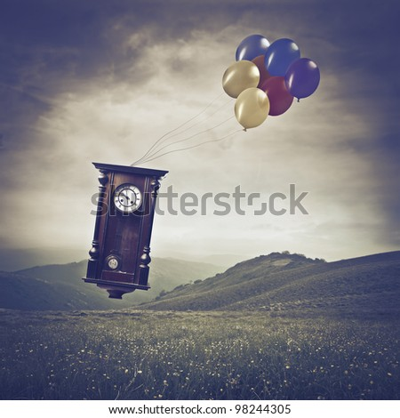 Pendulum flying over a meadow with some balloons - stock photo