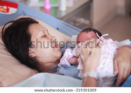 Penghu birth mother, a child lying on her chest. - stock photo