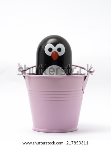 Penguin toy figure in the a bucket