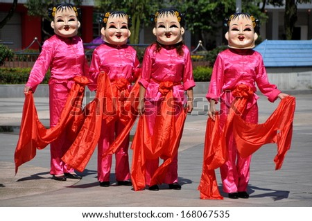 Pengzhou, Sichuan, China  Sept 25, 2012:  Four Chinese women wearing pink silk costumes with red silk scarves in full head masks dancing at a Mid-Autumn Festival  event in Pengzhou, China.