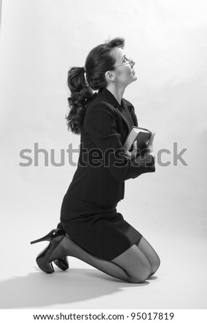 Penitent woman kneeling with her bible in black and white - stock photo
