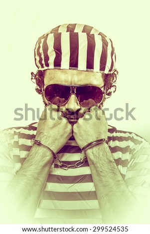 Penitentiary, Desperate, portrait of a man prisoner in prison garb, over white background - stock photo