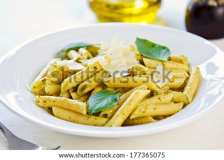 Penne in Pesto sauce with grated Parmesan on top - stock photo