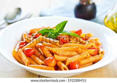 Penne in tomato sauce with basil on top - stock photo