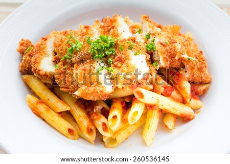 Penne in tomato sauce with deep fired chicken  - stock photo