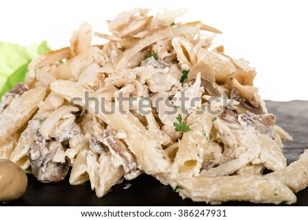 Penne Macaroni Pasta with Chicken and Mushroom and Parmesan Cheese with Tomato and Lettuce. Delicious Healthy Meal, Italian Pasta with Champignons and Sauce on Black Cutting Board Plateon Over White - stock photo