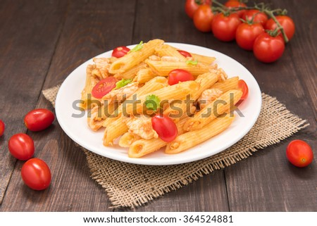 Penne pasta in tomato sauce with chicken on a wooden table. - stock photo