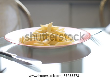 Penne pasta on white plate with red edges standing on glass table with natural light from window
