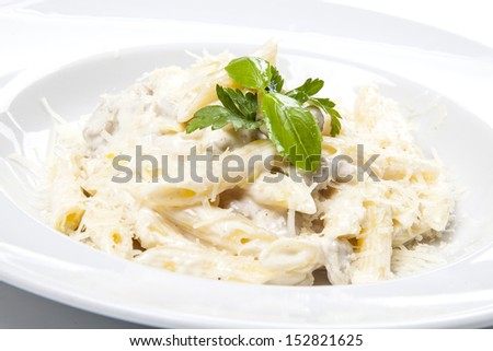 Penne pasta with a creamy sauce with parmesan cheese and basil on a white plate on a white background isolated - stock photo