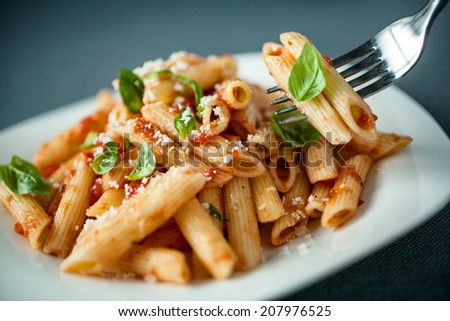 Penne pasta with a spicy sauce, basil and grated parmesan cheese with a forkful of pasta suspended above the plate with focus to the fork - stock photo