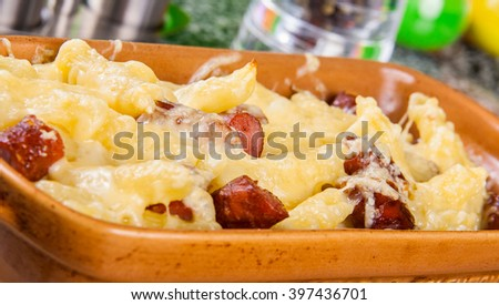 Penne pasta with cheese and sausages - stock photo