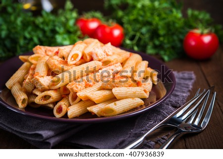 Penne pasta with chicken and tomato sauce on dark wooden background close up. Italian cuisine. - stock photo