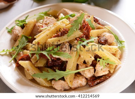 Penne pasta with chicken, dried tomatoes and ruckola - stock photo